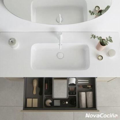 Vista superior de un lavabo con el cajón abierto, con todos los elementos de baño ordenados por separadores